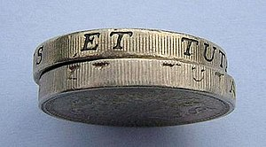 A real British pound coin on top of a fake. Th...