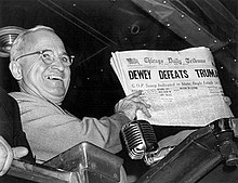 """Man in gray suit and wire glasses holding newspaper that says """"Dewey Defeats Truman"""""""