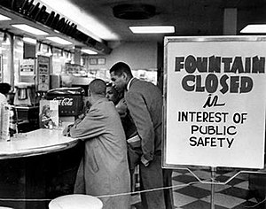 """Lunch counter with four young black men seated at bar stools along the counter. They are not being served and are simply sitting. A sign on the checkerboard-tiled floor reads """"Fountain closed in interest of public safety""""."""
