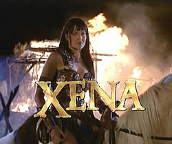 "A woman in leather armor sits on horseback with flames behind her. At the bottom of the screen in capital letters is the word ""Xena"" in gold lettering."