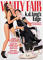Cover of Vanity Fair from 1993 showing short-haired k.d. lang sitting in a barber chair with shaving foam on her chin, reclining wearing a pinstripe pair of pants with cuffs tucked into black lace boots, open-collar dress shirt, and black and white striped tie, holding a compact mirror. Her eyes are closed. Supermodel Cindy Crawford wears a one-piece black bathing suit and high heel boots, holds lang's face to her breast and has her head thrown back so her long hair cascades down her back. Crawford holds a straight razor to lang's chin.
