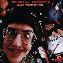 """The cover for Dare to Be Stupid features """"Weird Al"""" Yankovic's face against a backdrop of space. Scattered around his head are various items, such as a fish, a toaster, a toothbrush, and a hammer."""