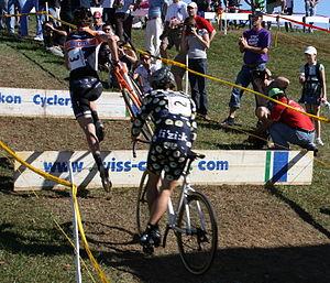 Photograph of cyclocross racer jumping over ba...