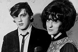 A young man and woman, in 1960s fashion, stand for a monochrome photograph. The man has a neutral expression on his face, the woman has a slight smile.
