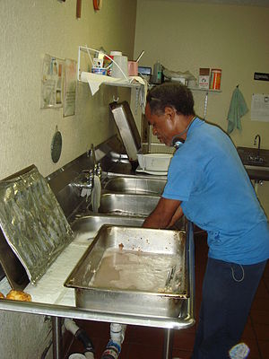 A volunteer washing dishes at Our Father's Hou...