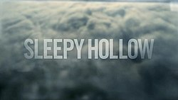 """The title """"Sleepy Hollow"""" is written over a town shrouded by clouds."""