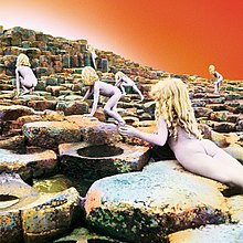 Six nude children with long blonde hair scramble up a stairstep series of basalt rocks ascending away from the viewer, with an orange-white sky above