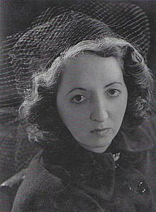 Manning as a young woman. She looks into the camera with a serious expression. Short, wavy hair is topped by a hat with veiling.
