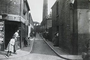 A cobbled slum street in a Deptford, London, C...
