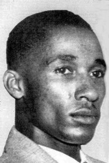 A black and white photograph of a young African American man with short hair in tight closeup.