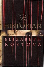 "Dark brown book cover saying ""The HISTORIAN""; then ""A Novel"" in a shiny gold stripe, then ""ELIZABETH KOSTOVA"". A few thin reddish streaks stretch from the top almost to the bottom."