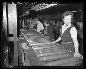 Women ordnance workers inspecting cartridge ca...