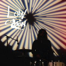 "A silhouette of a woman in front of a starburst design with the words ""LOW / C'MON"" written in white"