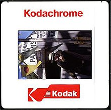 """A square white plastic frame, bearing the red text ""Kodachrome"" and a red logo bearing the word ""Kodak"", surrounds a portrait (rotated 90 degrees counter-clockwise) of a young woman wearing a white hat. She stands in front of a wooden building. Two triangular flags hang to the left, and the text ""Madam M Palmist"" is visible in the centre-top."""