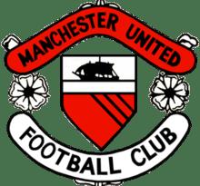 """Un blason de football. Au centre se trouve un bouclier avec un navire en pleine voile au-dessus d'un champ rouge avec trois lignes noires diagonales. De part et d'autre du bouclier se trouvent deux roses stylisées séparant deux rouleaux. Le parchemin supérieur est rouge et indique """"Manchester United"""" en noir, tandis que le parchemin inférieur est blanc avec """"Football Club"""", également écrit en noir."""