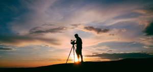 man using a video production camera on top of a mountin during sunset