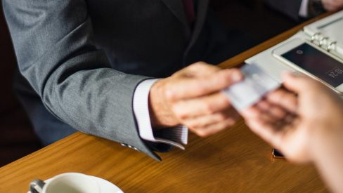 man handing over a business card to a woman at a coffee shop