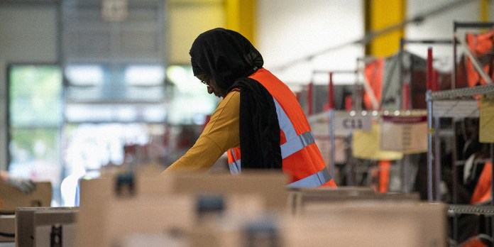 An Amazon employee inspects packages on an assembly line.