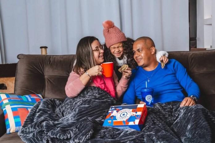 Mulher toma chocolate quente sentada no sofá ao lado de homem, ambos cobertos por uma manta. Eles são abraçados por uma criança de blusa de frio e touca
