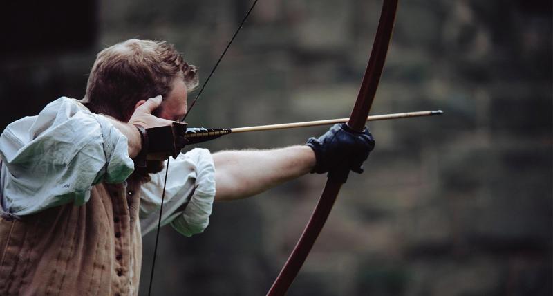 Hombre que sostiene un arco con el objetivo de un objetivo específico