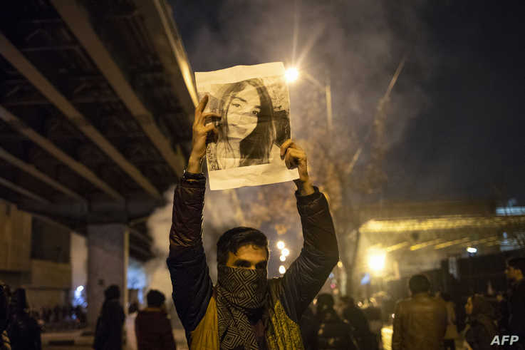 A protester holds up a picture of a victim of the downing by the Iranian military of a Ukrainian civilian airliner, during an anti-govenrnment rally outside Amir Kabir University, in Tehran, Iran, Jan. 11, 2020.