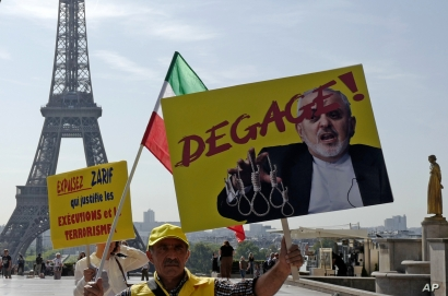 Demonstrators of the National Council of Resistance of Iran demonstrate on the Trocadero square Friday, Aug. 23, 2019 in Paris as Iranian Foreign Minister Javad Zarif is in France. Poster reads: get out