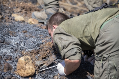 An Israeli soldier examines the remains of a rocket near the village of Avivim on the Israel-Lebanon border, Sept. 2, 2019.