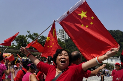 A pro-China supporter waves Chinese national flag at the Peak in Hong Kong Sunday, Sept. 29, 2019. Hundreds of pro-Beijing supporters sang Chinese national anthem and waved red flags ahead of China's National Day, in a counter to months-long pro…