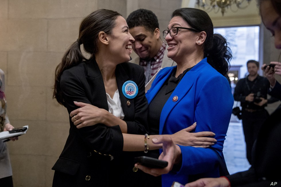 FILE - Rep. Alexandria Ocasio-Cortez, left, and Rep. Rashida Tlaib, laugh as they wait for other freshman Congressmen to deliver a letter calling to an end to shutdown to deliver to the office of Senate Majority Leader Mitch McConnell, Jan. 16, 2019.