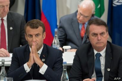 FILE - France's President Emmanuel Macron, left, and Brazil's President Jair Bolsonaro attend a meeting at the G-20 Summit in Osaka, June 28, 2019.