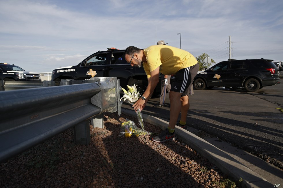 A man leaves flowers near the scene of a mass shooting at a shopping complex, Aug. 4, 2019, in El Paso, Texas.