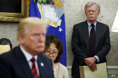 U.S. President Donald Trump, left, conducts a meeting in the Oval Office of the White House in Washington, May 22, 2018, as then-National Security Adviser John Bolton, right, looks on.