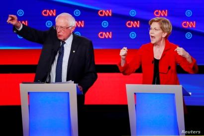 U.S. Senators Bernie Sanders (l) and Elizabeth Warren speak on the first night of the second 2020 Democratic presidential debate in Detroit, Michigan, July 30, 2019.