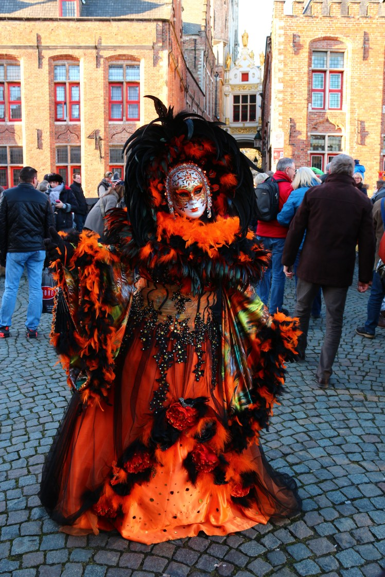 Amazing black and orange Venetian costumes in a parade on the streets of Bruges