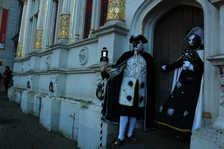 Black and white Venetian costumes, woman and man holding a walking stick/ lamp post, in Bruges old market square