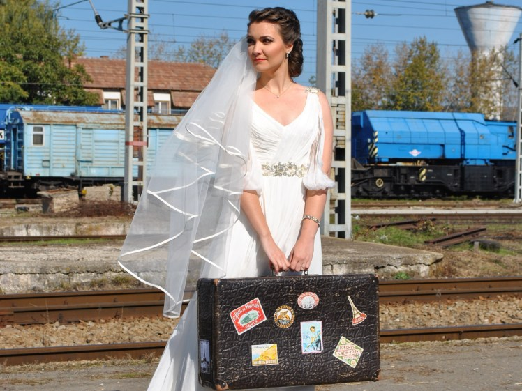 great travel expectations, bride with luggage in a train station