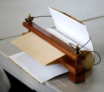 Book in fore edge painting press. Leather strap helps to reduce stress on the books binding.