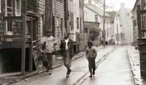 Three friends running in the rain up historic Pinkney Street, circa 1948