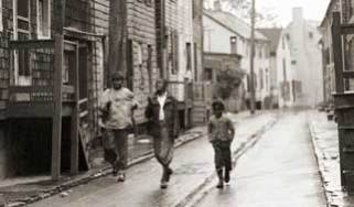 Three friends running in the rain up historic Pinkney Street, circa 1948