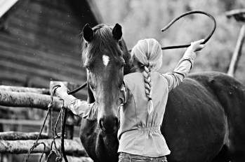 A rangler tacking up a horse for the day's morning ride at Triangle X Ranch, Jackson Hole, WY.