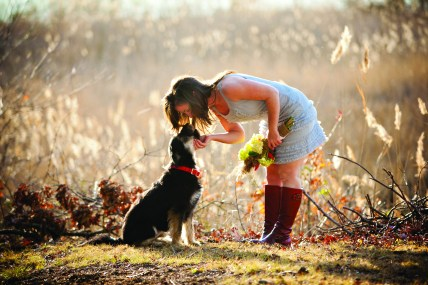 A tender moment between a bride and her dog on her wedding day.
