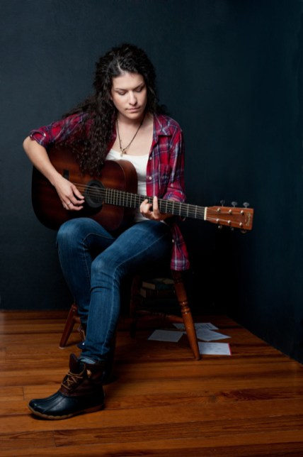 Jessie playing her guitar in the studio.