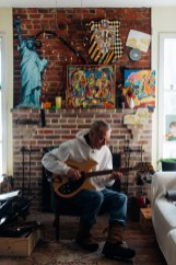 Russell Stone plays his twelve string guitar in front of some paintings by his brother Matt Stone in Annapolis, Maryland.