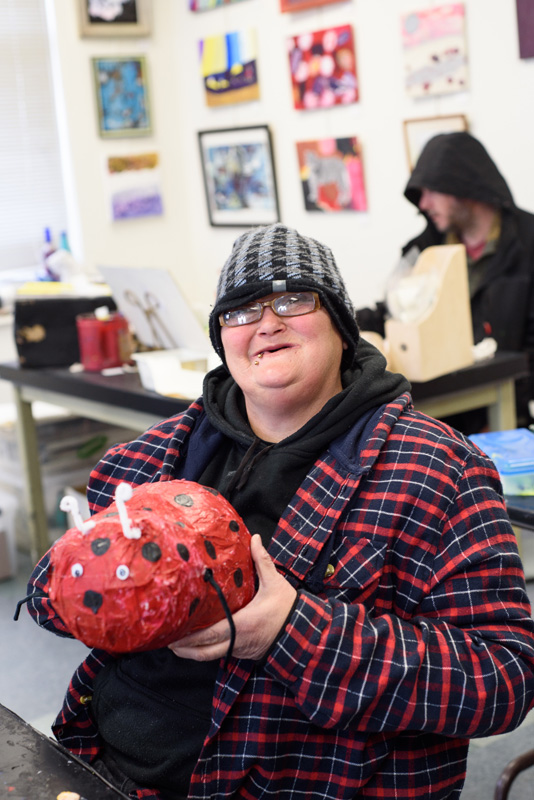 Wendy Berg proudly shows off her paper mache ladybug.