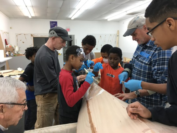Boat building instructors Jim Harmon and George Smith teach Box of Rain kids how to work with epoxy. Courtesy of Box of Rain