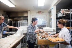 Owners Lucy Montgomery and Chris Simmons work with baker Stephanie Squires during their busy morning baking routine at Bakers and Co. in Eastport. Photo by Alison Harbaugh