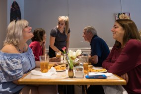 Server Lindsey Smith (center) chats with customers during the lunch rush at Evelyn's on September 26, 2018.