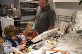 Michael and Evelyn help their father, owner Brandon Stalker, at the register.