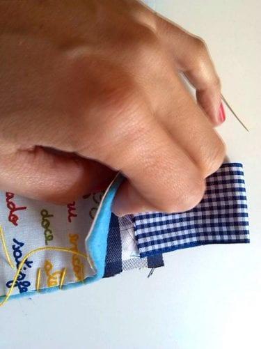 Colocar a fita numa das pontas do quadrado, entre os tecidos e o feltro.