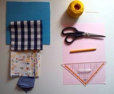 Material necessário: Feltro colorido, dois pedaços de tecido, Fita, Linha de crochet, tesoura, lápis de cor, régua/ esquadro, e cartolina ou folha de papel